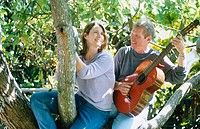 man with guitar serranaiding a woman