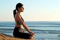 Indian girl meditating on beach at sunset, Carlsbad. California, USA