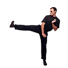 Man in black doing a karate style kick