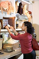 A woman checks the price on a decorative item on the shelf at a furniture store