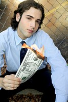 Portrait of a businessman holding a burning fifty dollar bill