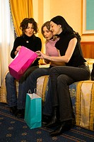 Three women share their purchases after shopping