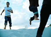 People running down sand dune, close-up