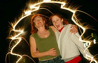 Mother and daughter surrounded by fireworks