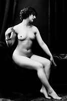 Circa 1920, nude woman sitting on drape covered bed holds right hand up to shoulder while looking down at left hand on knee