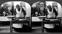 Woman in dress and apron standing behind table rolling out dough with a rolling pin
