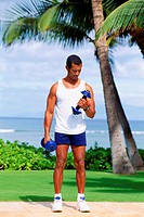 A male wearing athletic clothing, standing outdoors, lifting dumb bells