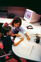 Overhead Side view of a businesswoman and her daughter sitting together at her office desk talking