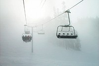 Chair lift on ski slope moves through foggy valley