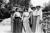 Group portrait of five woman wearing dresses and hats