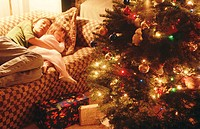Family. Christmas holidays. Mother and daughter (4 years old) sleeping on sofa next to tree