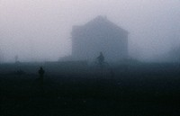 Silhouette of person on bike in front of house during heavy fog