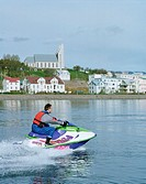 Man speeding on jet ski on sea, town of Akureyri in background