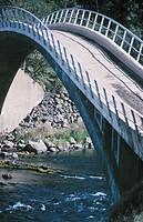 Narrow bridge and a river below.