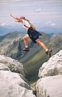Female hiker leaping across rocks. New Zealand.