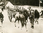 People wrapped in blankets walk on road with horse and wagon