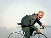 A bicyclist wearing a tailored suit