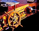 Wooden lacquered steering wheel and compass on a helm of an old speedboat