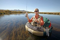 Woman flyfishing on a float tube on Silver Creek, Idaho. USA