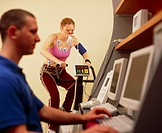 Fitness test. Woman taking a cardiovascular fitness test on an exercise bike. The scientist (left) monitors the recordings from equipment attached to ...