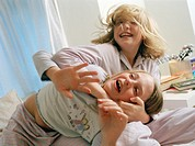 Twin girls playing. Ten-year-old twin girls play-fighting on a bed.