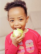Healthy eating. Four-year-old girl taking a bite from an apple. Apples are rich in minerals and vitamin C, as well as being low in fat.