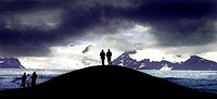 Two persons standing on top of a hill, snowy mountains in backround