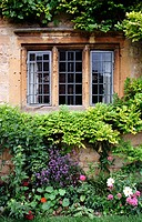 Flower garden framing the wrought iron window of a stone house in Chipping Campden, in the Cotswolds region of England