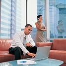 Businessman in an Office Lobby Sitting Using a Laptop and Businesswoman Using a Mobile Phone