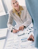 Businesswoman Sitting at a Desk With a Clipboard and Name Tags