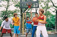 Girl Holding a Basketball Playing With Teenage Boys and Girls