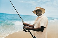 Portrait of a Mature Man Standing on the Beach at the Edge of the Sea Holding a Fishing Rod