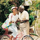 Elderly Couple Standing Laughinhg With a Bicycle in a Driveway