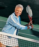 Portrait of a Mature Woman Standing Behind a Net on a Tennis Court Holding a Racket