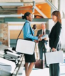 Two Businesswomen Talk as They Wait for Luggage on a Baggage Carousel