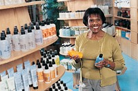 Smiling Woman in a Pharmacy Holding Bottles of Shampoo