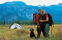 Hiking Couple Standing With Dog in Front of Moutain Range and Next to Tent