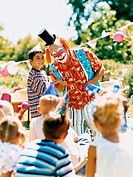 Clown Standing With Boy and Entertaining Children at a Birthday Party