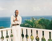 Man Standing With His Arms Folded on a Balcony Above a Tropical Sea Landscape