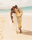 Newlywed Couple Walk in the Sand at the Waters Edge With Their Arms Around Each Other