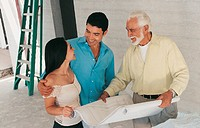 Couple With Their Arms Around Each Other Standing by a Senior Man Holding a Blueprint