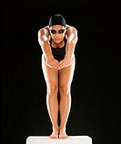 Adult Woman in Swimmming Costume Standing on Starting Block in Diving Position