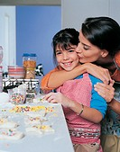 Mother Kissing Daughter as They Make Pastry Together