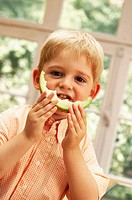 Little boy eating cantaloupe