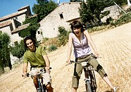 Carefree Young Couple Cycling in a Field