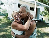 Couple Embrace With A Motor Home In The Background