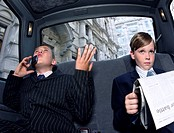 Two Boys Dressed as Businessmen in the back of a Taxi, one Reading a Newspaper the Other Gesturing Angerily and Using a Mobile Phone