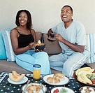 Couple Eating Breakfast on a Sofa with Food laid out on a Table