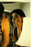 Asian woman putting on make up