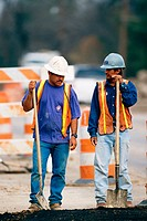 Construction workers leaning on shovels. Texas. USA